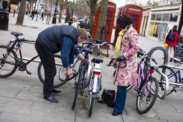 Two people locking up bikes